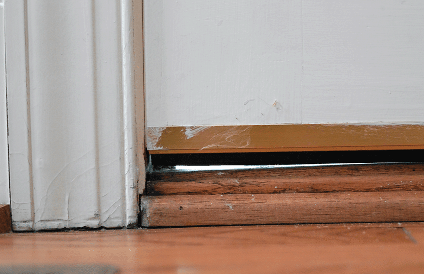 Drafty door due to a gap between the door and door sill.