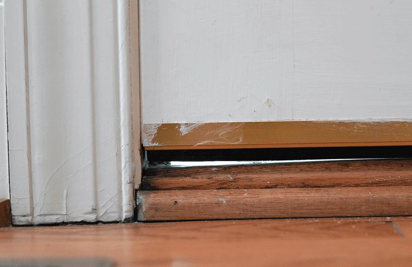 Drafty door due to a gap between the door and door sill.